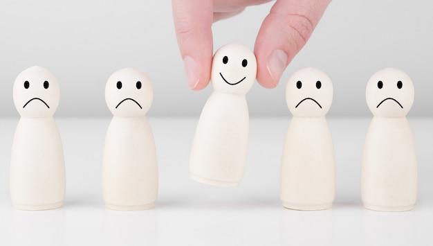 Hombre de madera con iconos que muestran emociones y puntuaciones. excelente calificación comercial. concepto de encuesta de satisfacción y experiencia en servicios al cliente.