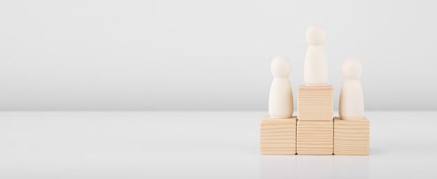 El hombre de madera que representa al líder acelera el éxito de pie en el pedestal
