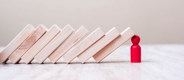 Hombre de madera rojo deja de caer bloques sobre la mesa. conceptos de negocio, planificación, gestión, líder, seguros, trabajo en equipo y estrategia de otoño