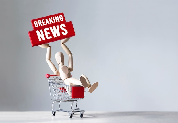 Hombre de madera sostenga un bloque de madera rojo con la palabra breaking news, concepto.