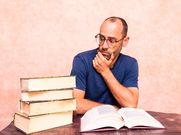 Hombre maduro agobiado por lo mucho que debe leer para aprender el mundo de los abogados y el derecho