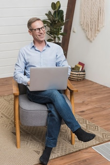 Hombre maduro de alto ángulo usando una laptop