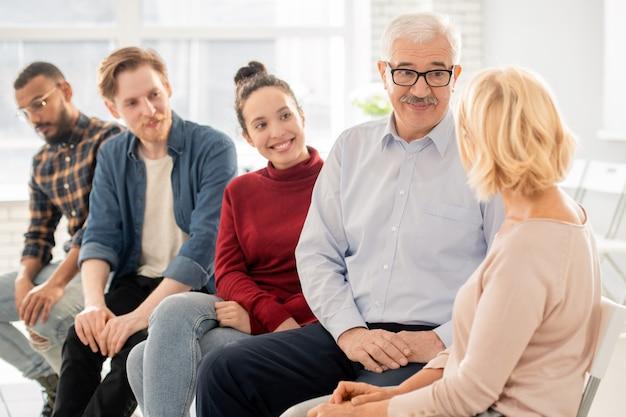 Hombre maduro en anteojos y ropa casual hablando con una mujer rubia de su edad en la sesión junto a jóvenes compañeros de grupo