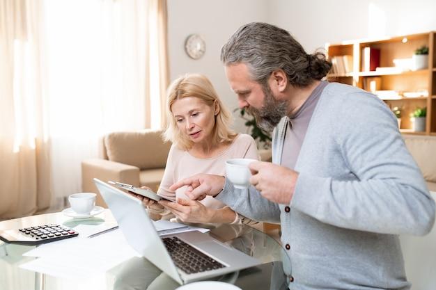 Hombre maduro con barba con una taza de té apuntando al documento sostenido por su esposa mientras ambos lo miran