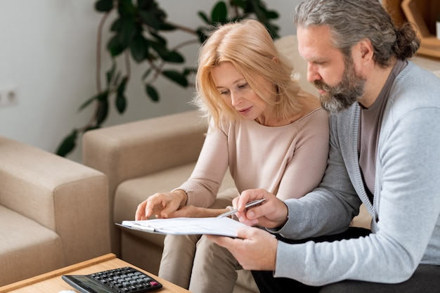 Hombre maduro barbudo apuntando al contrato de compra de una casa nueva mientras lo lee con su esposa antes de firmar