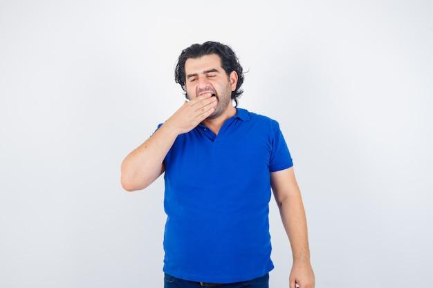Hombre maduro bostezando en camiseta azul y con sueño. vista frontal.