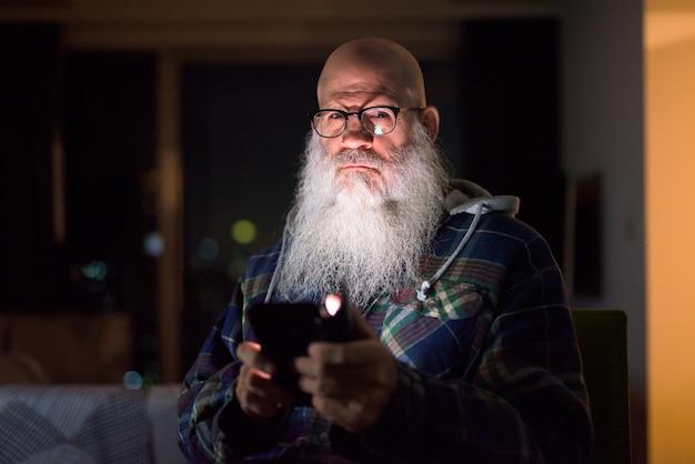 Hombre maduro calvo barbudo hipster pensando mientras usa el teléfono en casa en la oscuridad