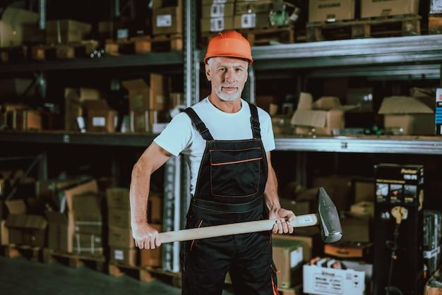 Hombre maduro en casco protector con martillo