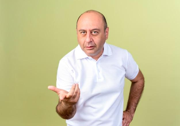 Hombre maduro confundido apunta y poniendo la mano en la cadera aislado en la pared verde oliva