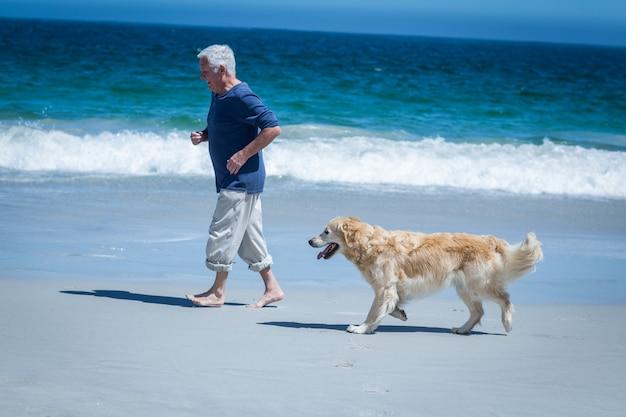 Hombre maduro corriendo junto a su perro
