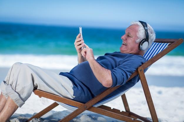 Hombre maduro descansando en una tumbona escuchando música con smartphone
