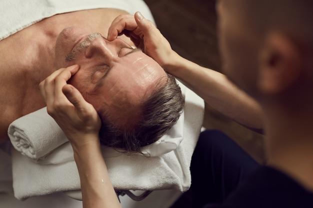 Hombre maduro disfrutando de un masaje facial en spa