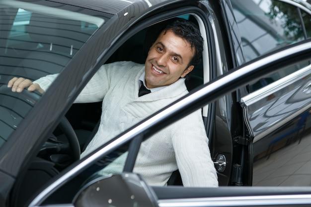 Hombre maduro, elegir un coche nuevo en el salón del concesionario