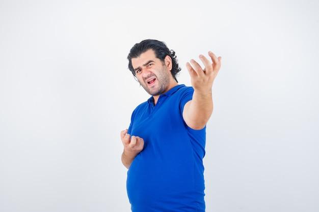 Hombre maduro estirando la mano como sosteniendo algo imaginario en camiseta azul, jeans y mirando enojado. vista frontal.