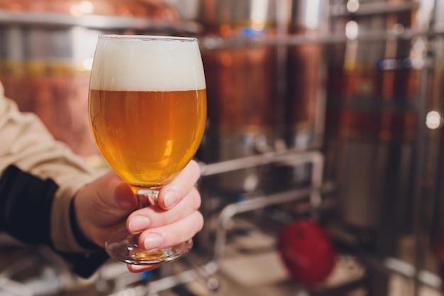 Hombre maduro examinando la calidad de la cerveza artesanal en la cervecería. inspector trabajando en la fábrica de fabricación de alcohol comprobación de cerveza. hombre en destilería control de calidad de cerveza de barril.