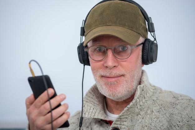 Hombre maduro con gorra en auriculares escuchando música en casa