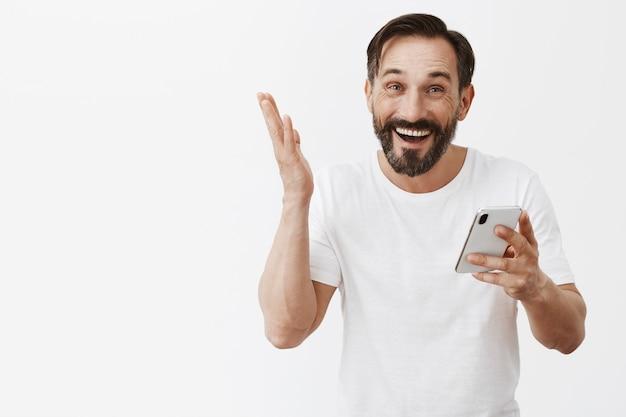 Hombre maduro guapo con barba posando con su teléfono
