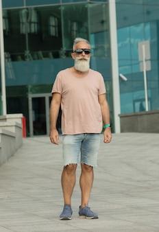 Hombre maduro guapo caminando en la ciudad. hombre mayor barbudo.