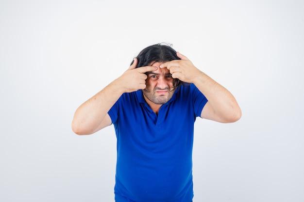 Hombre maduro haciendo estallar la espinilla en camiseta azul, jeans y mirando enfocado. vista frontal.