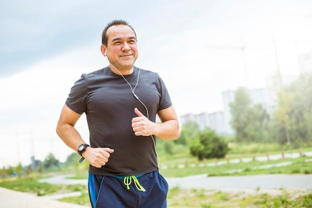 Hombre maduro haciendo footing en una calle de la ciudad. senior hombre lleva un estilo de vida saludable y activo haciendo deporte.