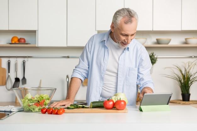 Hombre maduro hermoso que se coloca en la cocina que cocina la ensalada.