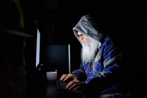 Hombre maduro hipster barbudo con anteojos trabajando horas extras en casa en la oscuridad