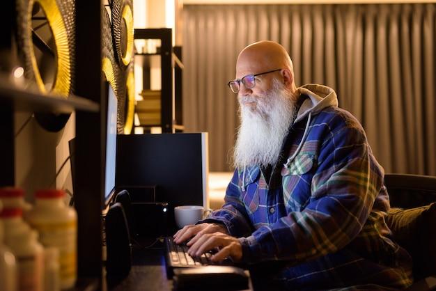 Hombre maduro hipster barbudo calvo trabajando horas extras en casa por la noche