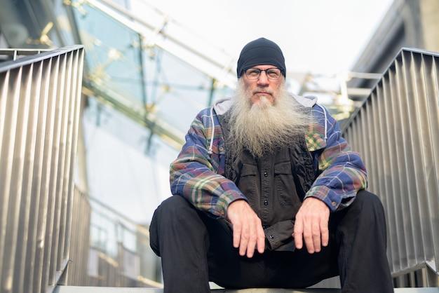 Hombre maduro hipster barbudo sentado en la pasarela en la ciudad