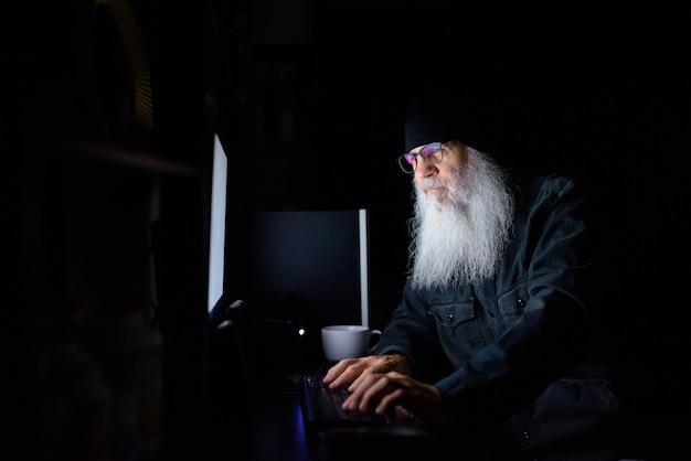 Hombre maduro hipster barbudo trabajando horas extras en casa por la noche en la oscuridad