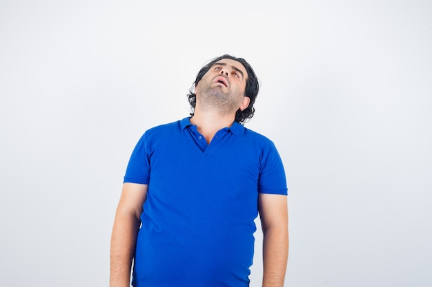 Hombre maduro, inclinando la cabeza hacia atrás en camiseta azul y mirando con sueño. vista frontal.