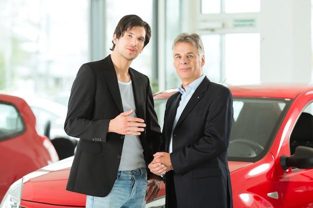 Hombre maduro y joven con autos en concesionario de automóviles