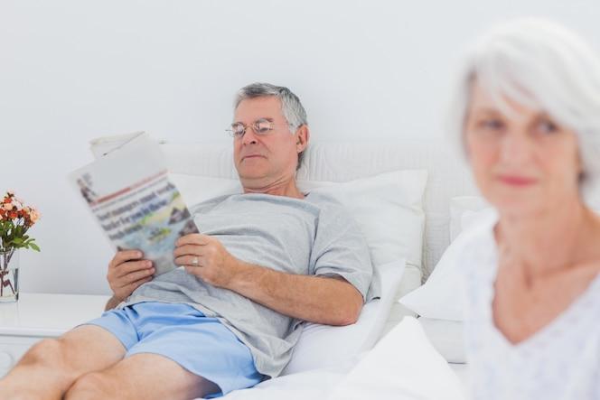 Hombre maduro leyendo un periódico en la cama