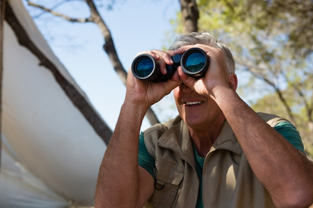 Hombre maduro mirando a través de binoculares