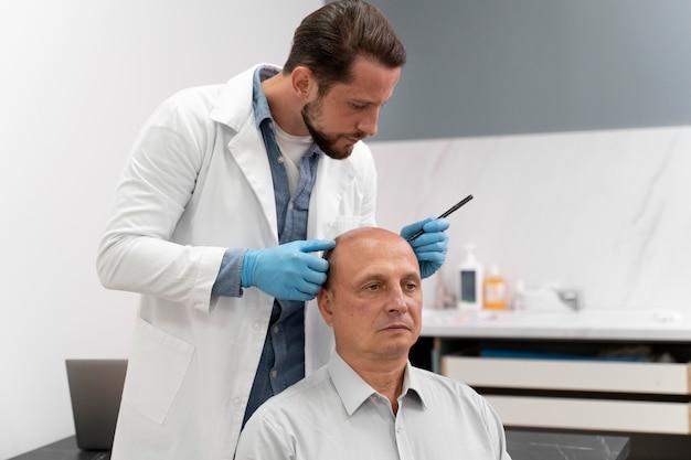 Hombre maduro, pasando por un proceso de extracción de unidades foliculares