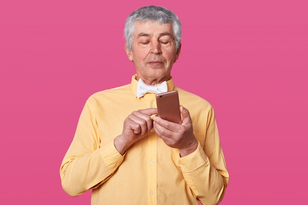 Hombre maduro de pelo blanco vestido con camisa amarilla y corbata de moño blanco, sosteniendo el teléfono inteligente en las manos y mensajes tipo