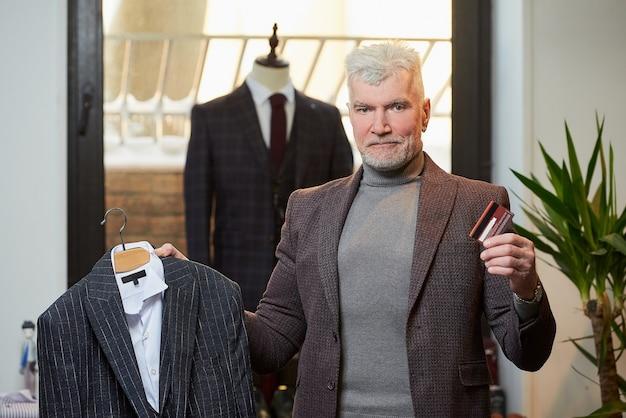 Un hombre maduro de pelo gris y físico deportivo posa con un traje de lana y una tarjeta de crédito en una tienda de ropa. un cliente masculino con barba viste un traje en una boutique.