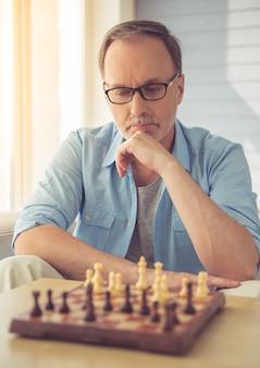 Hombre maduro pensativo en anteojos está jugando al ajedrez.