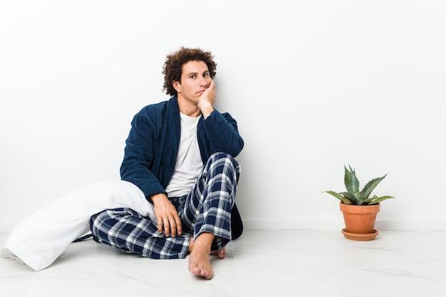 Hombre maduro con pijama sentado en el piso de la casa que está aburrido, cansado y necesita un día de relax.