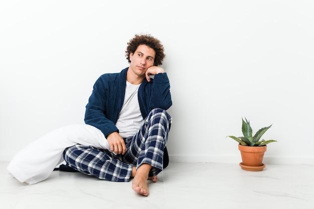 Hombre maduro con pijama sentado en el piso de la casa que se siente triste y pensativo, mirando el espacio de la copia.