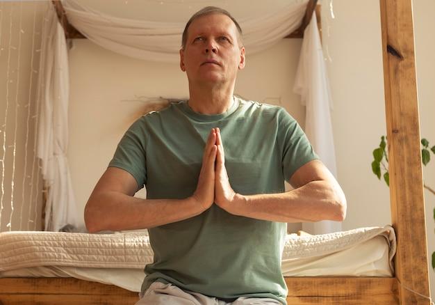 Hombre maduro, practicar yoga y meditar en casa acogedora con las manos juntas en pose de meditación