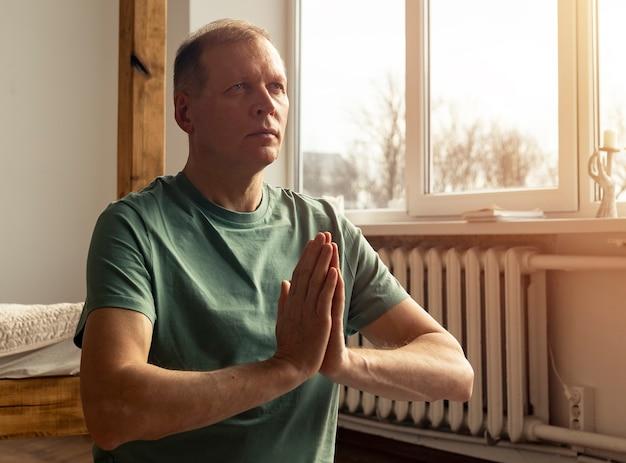 Hombre maduro, practicar yoga y meditar en casa acogedora con las manos juntas