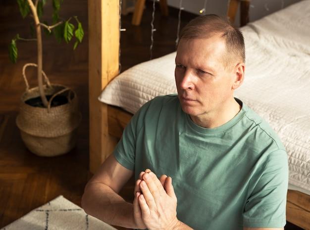 Hombre maduro, practicar yoga y meditar en casa acogedora