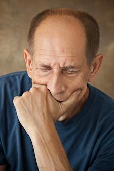 Hombre maduro preocupado tocando su cabeza.