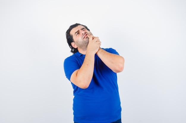Hombre maduro que sufre de dolor de muelas en camiseta azul y parece doloroso. vista frontal.