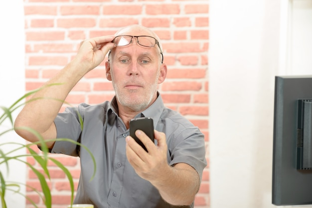 Hombre maduro que tiene problemas para ver la pantalla del teléfono debido a problemas de visión