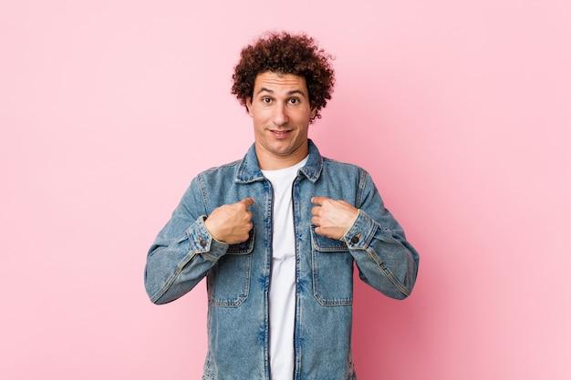 Hombre maduro rizado con una chaqueta de mezclilla sobre fondo rosa sorprendido señalando con el dedo, sonriendo ampliamente.
