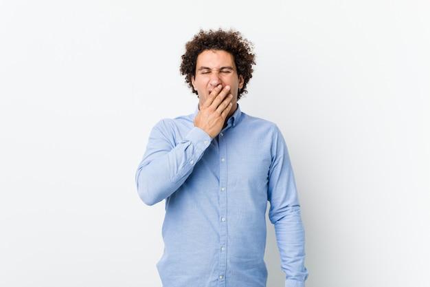 Hombre maduro rizado joven que lleva una camisa elegante que bosteza mostrando un gesto cansado que cubre la boca con la mano.