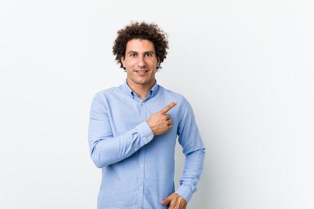 Hombre maduro rizado joven que llevaba una camisa elegante sonriendo y apuntando a un lado, mostrando algo en el espacio en blanco.