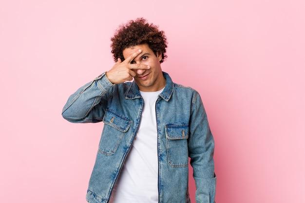 Un hombre maduro y rizado que llevaba una chaqueta de mezclilla contra la pared rosada parpadea a través de los dedos, avergonzado cubriéndose la cara.