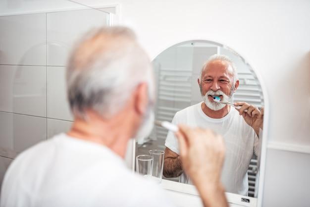 Hombre maduro sonriente que cepilla sus dientes en el cuarto de baño por la mañana.
